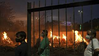 People watch burning funeral pyres of their relatives who died of COVID-19 in a ground that has been converted into a crematorium in New Delhi, India, Thursday, May 6, 2021.