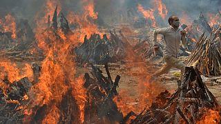 یک مرد از گرمای آتش جنازه سوزی در دهلی نو میگریزد/ ۲۹ آوریل