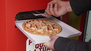 Elkészült pizzát vesz ki egy férfi az automatából