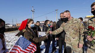 Koszovói albán nők virágot nyújtanak át amerikai békefenntartóknak, januárban