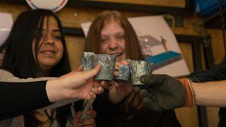 A folyóból kihalászott műanyagból készült poharak tiszadadai diákok kezében