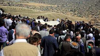 Afghan men bury a victim of the deadly bombings that killed more than 50 on Saturday