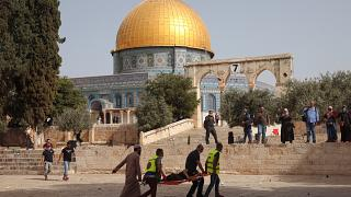 Palestinians evacuate a wounded man during clashes with Israeli security forces in front of the Dome of the Rock Mosque