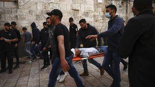 فلسطينيون بحملون متظاهرا مصابا خلال مواجهات مع قوات الأمن الإسرائيلية قرب باب الأسباط، البلدة القديمة بالقدس، الإثنين، 10 مايو، 2021