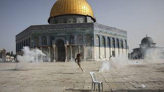 فلسطيني يهرب من الغاز المسيل للدموع خلال مواجهات مع قوات الأمن الإسرائيلية أمام مسجد قبة الصخرة في الحرم الأقصى