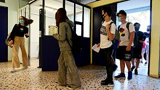 Students wearing face masks to help curb the spread of the coronavirus, wait to check their temperature at a junior high school in Athens, Monday, 10 May, 2021.