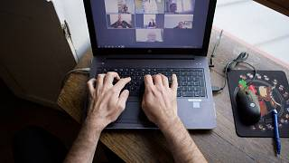 A man works from home as multinationals seek to make remote work permanent.