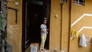 طفلة عراقية تقف على عتبة منزل ذويها وإلى جانبها سلة مساعدات غذائية تقدمة الجمعيات الخيرية في مدينة الموصل شمال البلاد خلال شهر رمضان المبارك