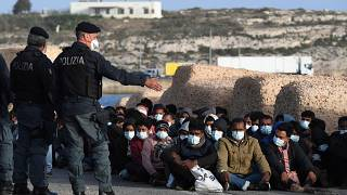 Les migrants arrivés sur l'île de Lampedusa en Italie attendent sur le quai, le 10 mai 2021