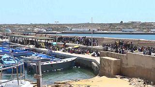 An den Kaianlagen im Hafen von Lampedusa drängen sich die Menschen ohne Schutz vor der Sonne