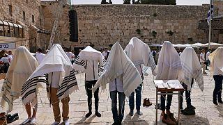 يهود يرتدون شالات الصلاة اليهودية التقليدية المعروفة باسم تاليت بالقرب من الحائط الغربي، أقدس موقع يُسمح لليهود بالصلاة فيه في البلدة القديمة في القدس