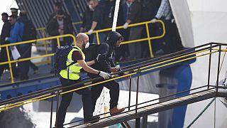 Un agente de la agencia de protección de fronteras de la Unión Europea, Frontex, conduce a un migrante para que embarque en un transbordador en Grecia en 2016