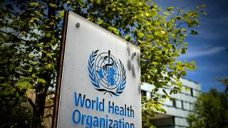 يافطة تحمل شعار منظمة الصحة العالمية أمام مكتبها في مدينة جنيف السويسرية