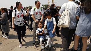 """Residents wearing t-shirts which reads """"Made In China"""" visit Tiananmen Gate with two children in Beijing"""
