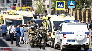 Los bomberos pasan por delante de ambulancias y coches de policía y un camión aparcado en una escuela después de un tiroteo en Kazán, Rusia, el martes 11 de mayo de 2021.