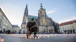 Egy katona meggyújtja a koronavírus csehországi áldozatainak emlékére elhelyezett közel 30 ezer mécses egyikét a prágai várnál 2021. május 10-én