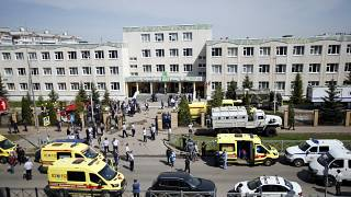 Ambulances and police cars and a truck are parked at a school after a shooting in Kazan, Russia, Tuesday, May 11, 2021.