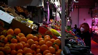 A woman checks fruit and vegetables at the Cebada market in Madrid