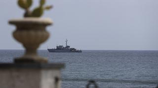 An Italian navy ship patrols the waters in front of the Sicilian town of Taormina in the Mediterranean Sea.