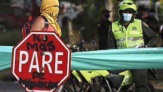 Un manifestantes y un policía en Cali, Colombia
