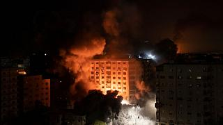 Smoke caused by Israeli airstrikes are seen at a residential building in Gaza City