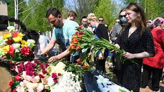 Mourners lay flowers at the grave of English teacher Elvira Ignatyeva.