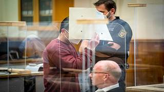 المتهم السوري، إياد الغريب، يخفي وجهه في قاعة محكمة بمدينة كوملنز الألمانية التي أدانته في 24 شباط/فبراير 2021 بارتكاب جرائم تتعلق بتعذيب السجناء أثناء عمله ضمن مخابرات النظام