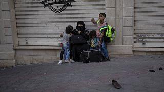 İsrail'in Gazze'ye yönelik hava bombardımanında evleri bombalanan bir aile, yol kenarında beklerken