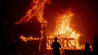A home burns as a wildfire called the Camp Fire rages through Paradise, Calif.