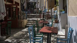 Chairs with a seat removed are placed around tables at a closed restaurant in the Athens' historic Plaka district, on Friday, April 30, 2021