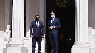 Greek Prime Minister Kyriakos Mitsotakis, right, and his North Macedonian counterpart Goran Zaev stand at the entrance of Maximos Mansion