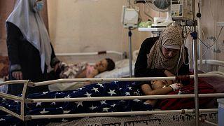 The mother of Yazan Al-zaharna, 9, comforts him as he rests at the Shifa hospital in Gaza City, Thursday, 13 May, 2021.