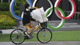 Az olimpiai ötkarika előtt halad el egy védőmaszkos kerékpáros Tokióban 2021. május 13-án.