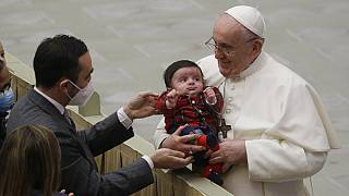 Pope Francis cuddles a baby as he exchanges holidays greeting with Vatican employees in December 2020