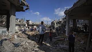 Palestinians inspect their destroyed houses following overnight Israeli airstrikes
