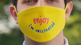 """كمامة كُتب عليها """"استمتع لقد تلقيتُ اللقاح"""""""