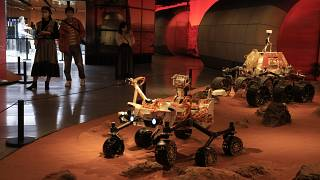 Visitors pass by an exhibition depicting rovers on Mars in Beijing on Friday, May 14, 2021.