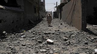 رجل يمشي فوق ركام مبنى دمره القصف الإسرائيلي