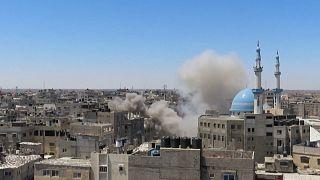 Israeli airstrike hitting the town of Rafah, smoke billowing.