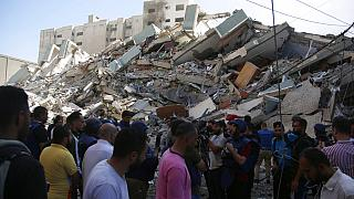 People gather at in front of a building housing AP office and other media in Gaza City