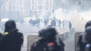 Protesters, surrounded by tear gas, face French riot mobile gendarmes in Paris.