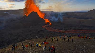 People watch as lava flows from an eruption from the Fagradalsfjall volcano on the Reykjanes Peninsula in southwestern Iceland on Tuesday, May 11, 2021.