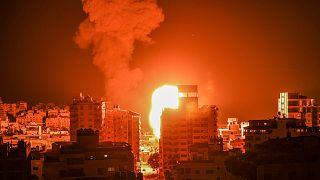 نيران ودخان يتصاعدان فوق المباني في مدينة غزة مع استهداف الطائرات الحربية الإسرائيلية للجيب الفلسطيني ، في وقت مبكر من يوم 17 مايو ، 2021.