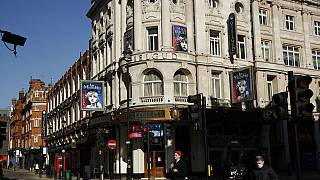 In this Friday, Feb. 26, 2021 file photo, signs for Les Miserables are displayed on the temporarily closed Gielgud Theatre during England's third coronavirus lockdown.