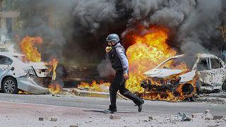 یک آتشنشان اسرائیلی در اطراف خودرویی که به دلیل برخورد راکت حماس آتش گرفته است. اشکلون، اسرائیل.