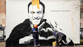 عمال البلدية يزيلون رسماً جدارياً يظهر فيه نافالني، في سانت بطرسبرغ 28 أبريل 2021