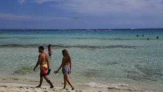 A couple walk at the beach as other enjoy the sea water in the southeast resort of Ayia Napa in Cyprus