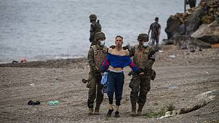 A man from Morocco is detained by soldiers of the Spanish Army at the border of Morocco and Spain, at the Spanish enclave of Ceuta, on Tuesday, May 18, 2021