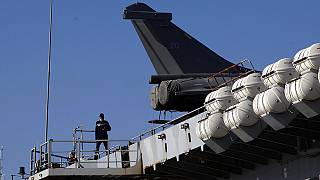 A French crew member walks on France's nuclear-powered aircraft carrier Charles de Gaulle at Limassol port, Cyprus,