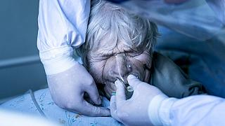 A medic wearing a special suit against coronavirus adjusts a coronavirus patient's oxygen mask at the intensive care unit at a hospital in the mining town of Selydove, Ukraine